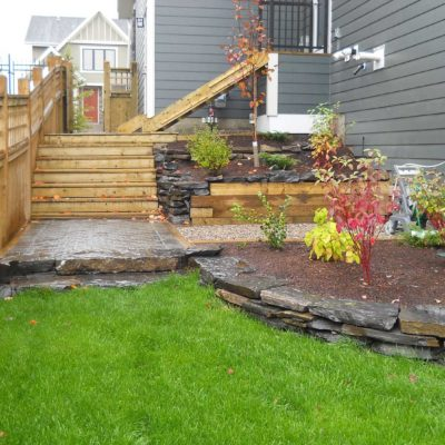 After Backyard Transformation Garden with Wooden Stairs and Natural Stone Flower Border Before After by European Garden Design Calgary