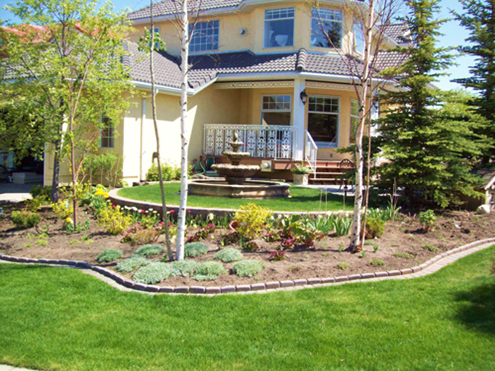 Backyard Oasis Yellow House By European Garden Design Calgary