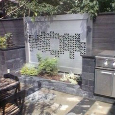 Backyard Patio Seating Area Stone Fence Decoration Artwork by European Garden Design Calgary