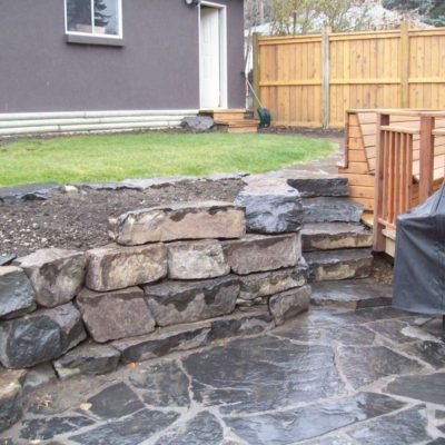 Stonework Fencing and Deck and Retaining Wall by European Garden Design Calgary