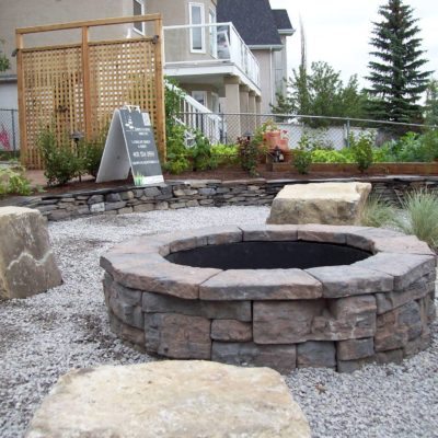 Natural Stone Backyard Firepit with Seating Stonework by European Garden Design Calgary